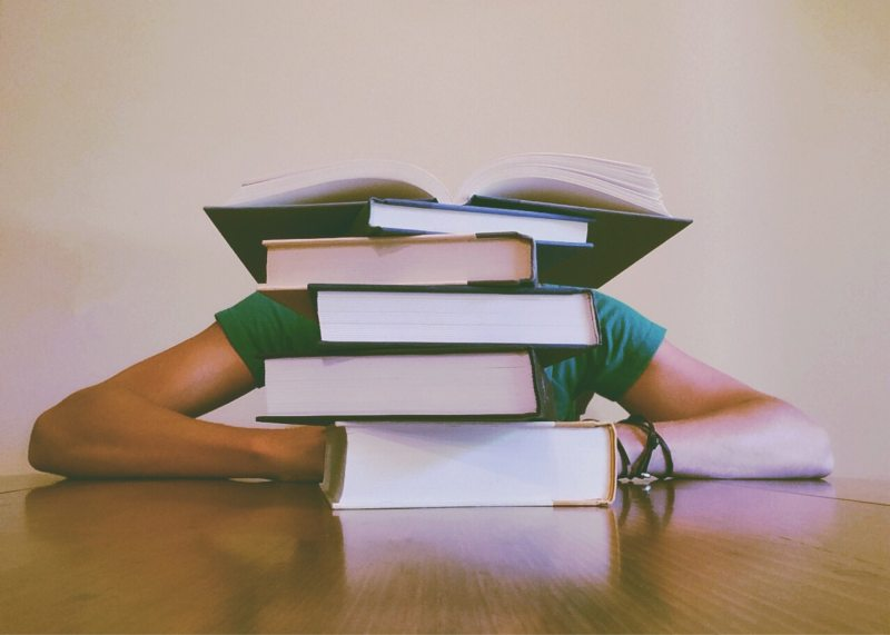 Student hiding behind a tall pile of books