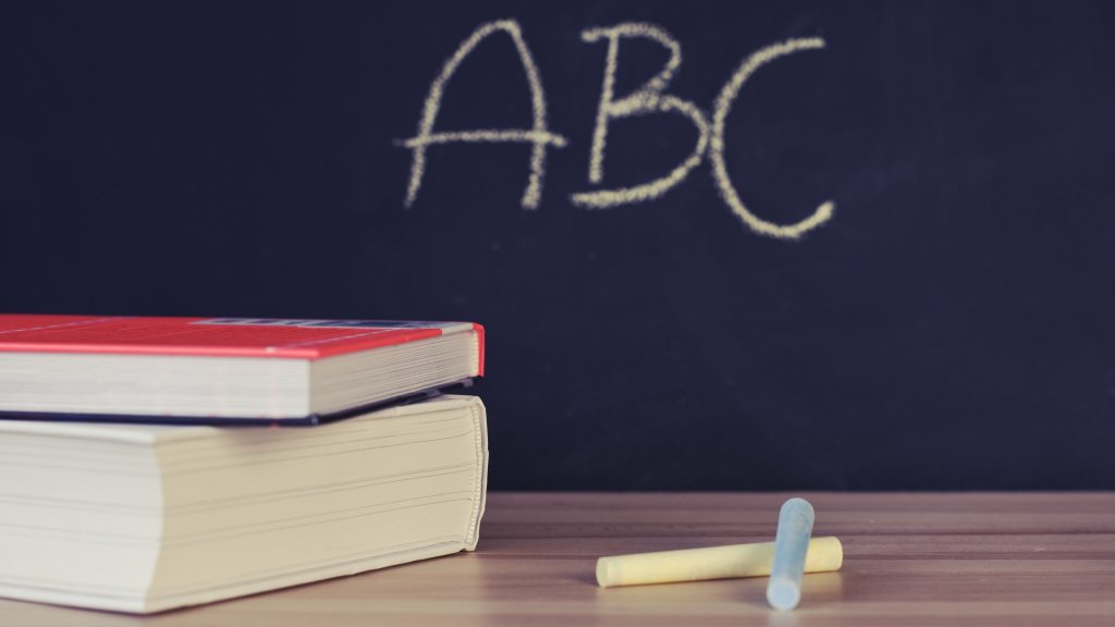 Stack of books in front of a chalkboard